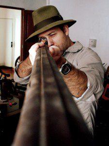 Man met geweer gericht op de kijker